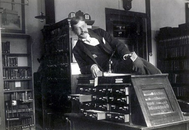 The Original Sexy Librarian. Vintage photo, male librarian strikes a pose on top of the card catalog. Talk Dewey To Me. marchmatron.com