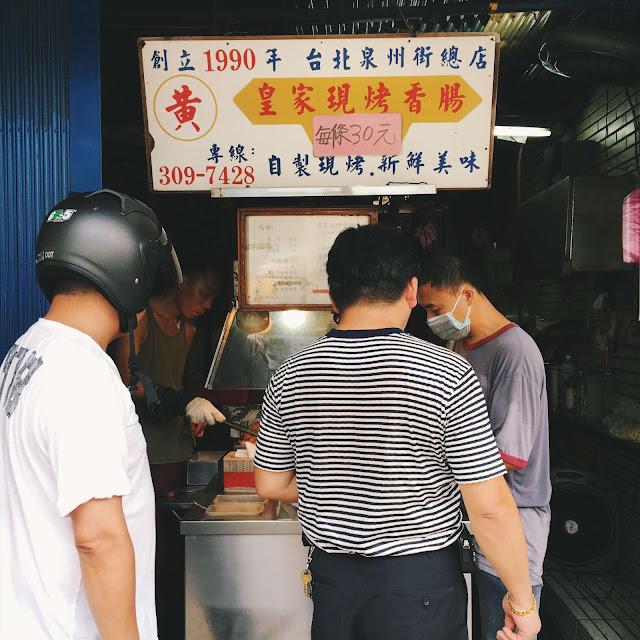 皇家烤香腸,就位在中正區的泉州街上,還沒到店門口,就聞到一股烤香腸的炭香味,排隊的每個人緊捏著鈔票和銅板,眼睛死盯著躺在炭火上那一根根排列整齊的烤香腸。