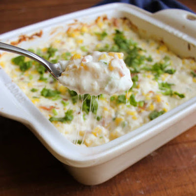 spoon pulling out serving of warm corn dip with cheesy strings