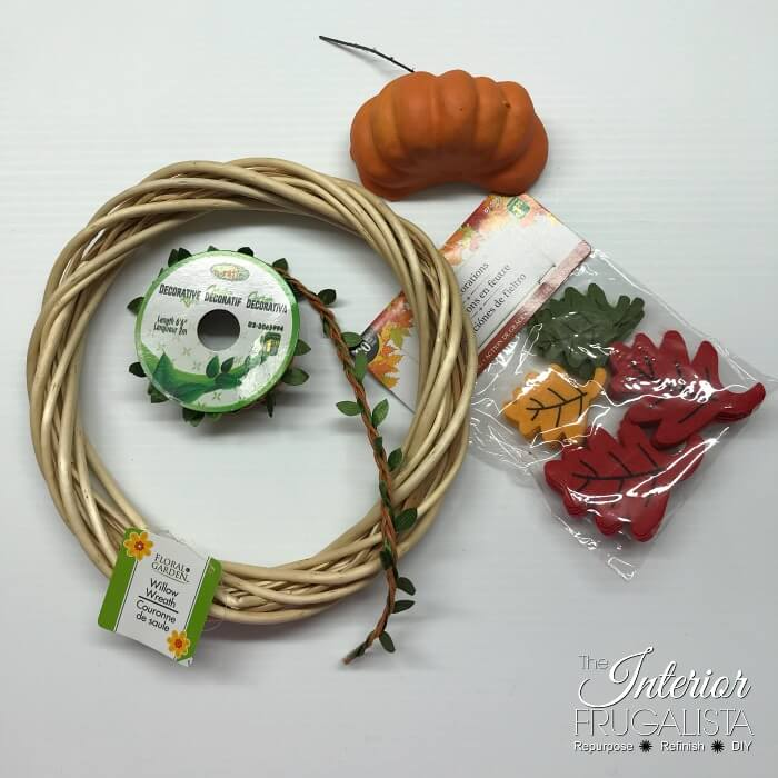 Turn inexpensive dollar store finds into an adorable small DIY Fall Pumpkin Wreath and it's so quick and easy to make in five minutes or less.