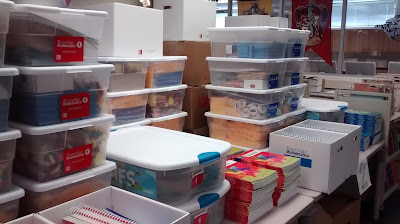 Stacked clear bins with white lids, containing miscellaneous items, along with books in stacks or upright inside lidless boxes covering a large table-top surface