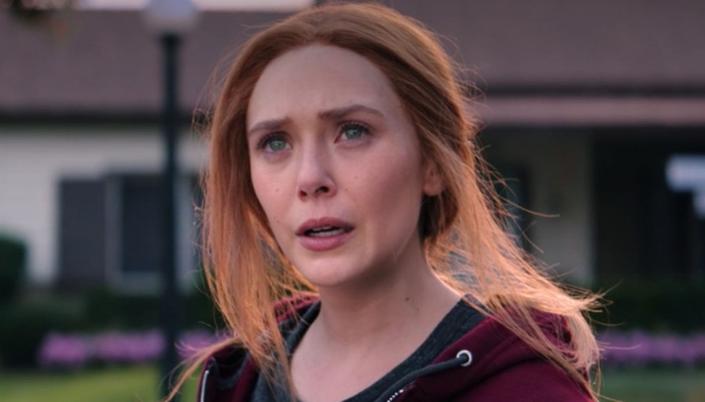 Imagem: Wanda, uma mulher branca de cerca de 30 anos de olho azul e cabelo ruivo e longo está olhando com cara de preocupada e usa um moletom vermelho e o fundo é uma casa desfocada.