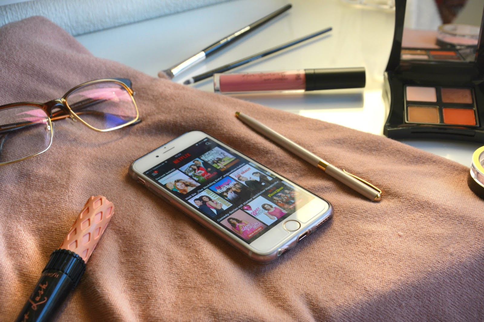 Netflix App on dusty pink background with glasses, Illamasque eyeshadow, Benefit Rollerlash, nude lipstick and Maxfactor Blush