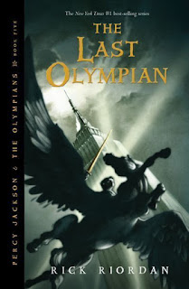 A boy (Percy) holding a sword flies on a Pegasus in the shadow of the Empire State Building