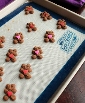 bear shaped chocolate spritz cookies with red and pink heart candies on top ready to be baked
