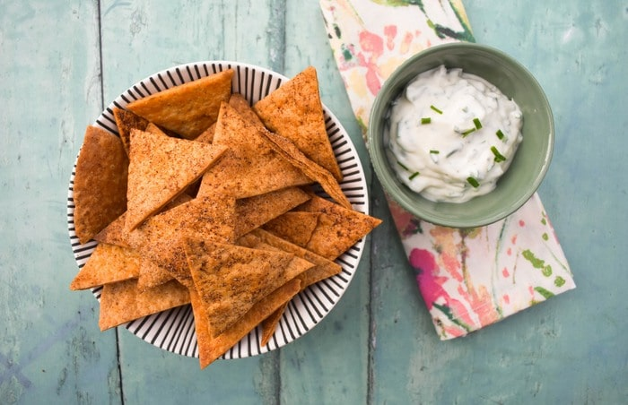 A bowl of tortilla chips next to a smaller bowl of lemon and chive dip