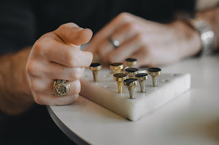 A man's hand, wearing a signet ring.