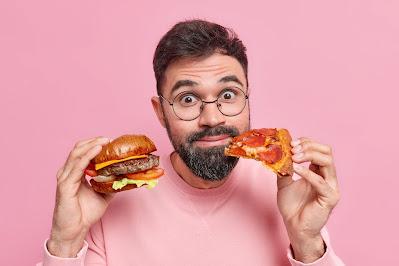 Persona con hamburguesa y un pedazo de pizza
