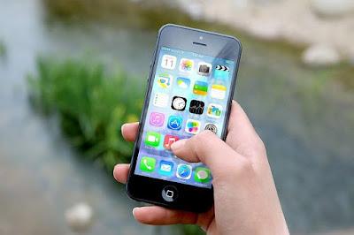 Hand som håller en mobilelefon.