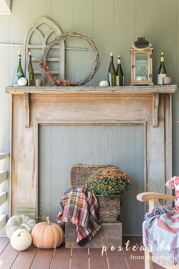 rustic outdoor mantel with pumpkins and wine bottle luminaries