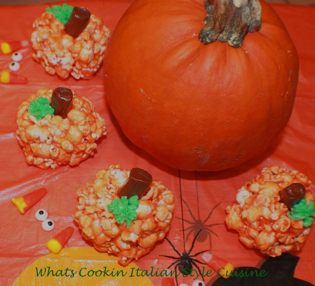 these are easy popcorn balls for Halloween shaped into pumpkin heads rice krispie treats recipe