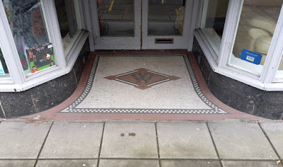 The mosaic tile logo at the old Woolworths on Stamford Street Central in Ashton-under-Lyne, Tameside, Greater Manchester