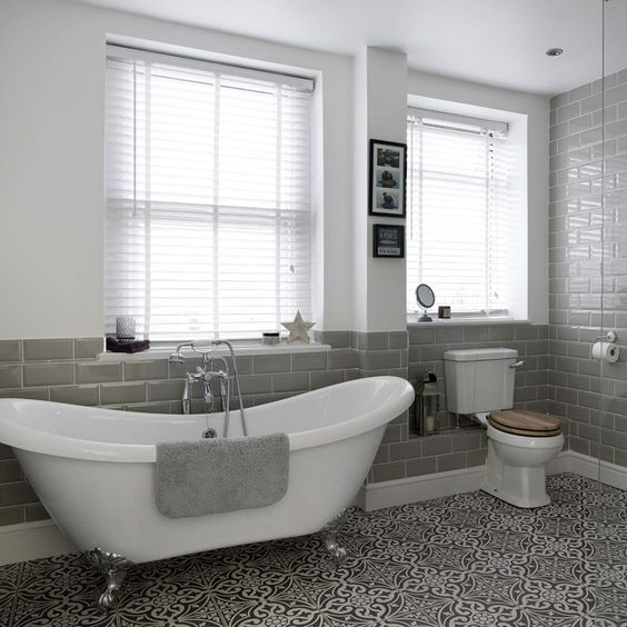 freestanding bath, grey towels and accessories, tiled floor