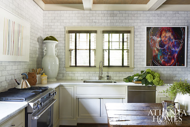 White eclectic kitchen with stainless appliances and modern art