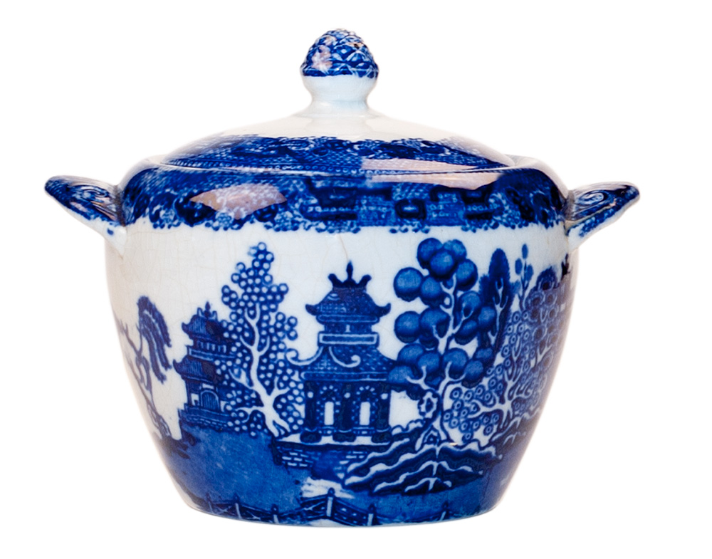 A vintage handled sugar bowl with lid decorated with the blue willow pattern.