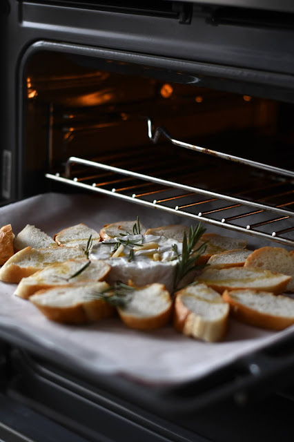 Oven with bread and cheese being placed in:Photo by Raspopova Marina on Unsplash