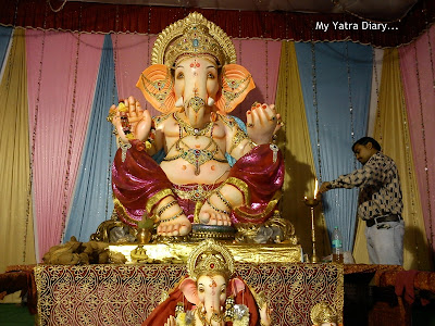 A large Ganpati idol  in Mumbai Pandal decorated with coconuts, fruits and flowers