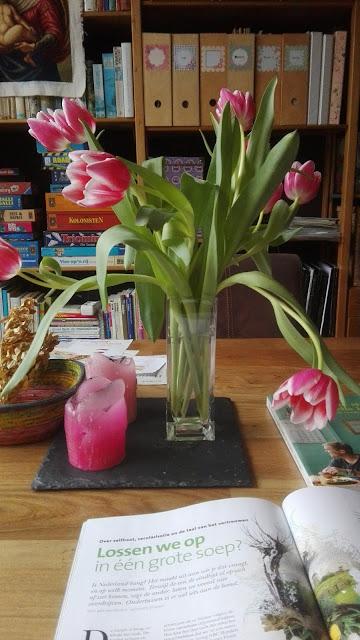 Bos wit-roze tulpen op een houten tafel met een tijdschrift en ene kookboek.