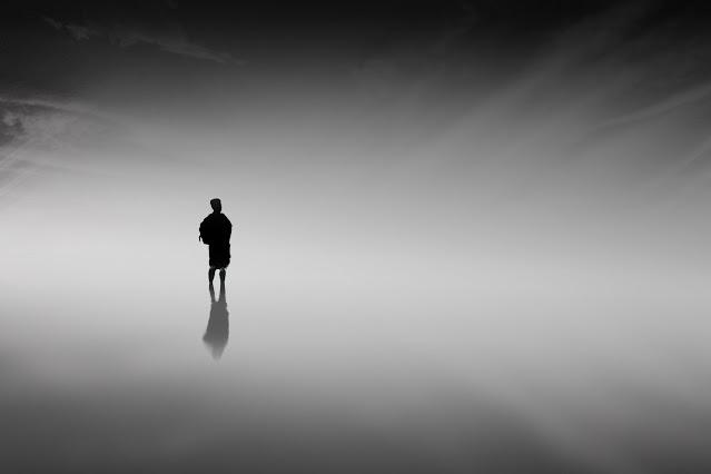 imagen de una persona en una playa en bajamar en un ambiente oscuro del amanecer