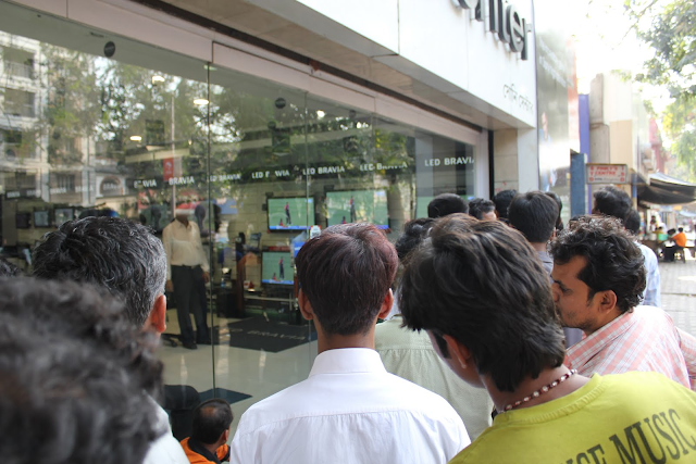 Cricket fans outside an electronics shop watching a cricket match