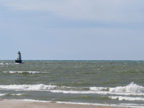 Lake Michigan with green waves and Ludington Lighthouse