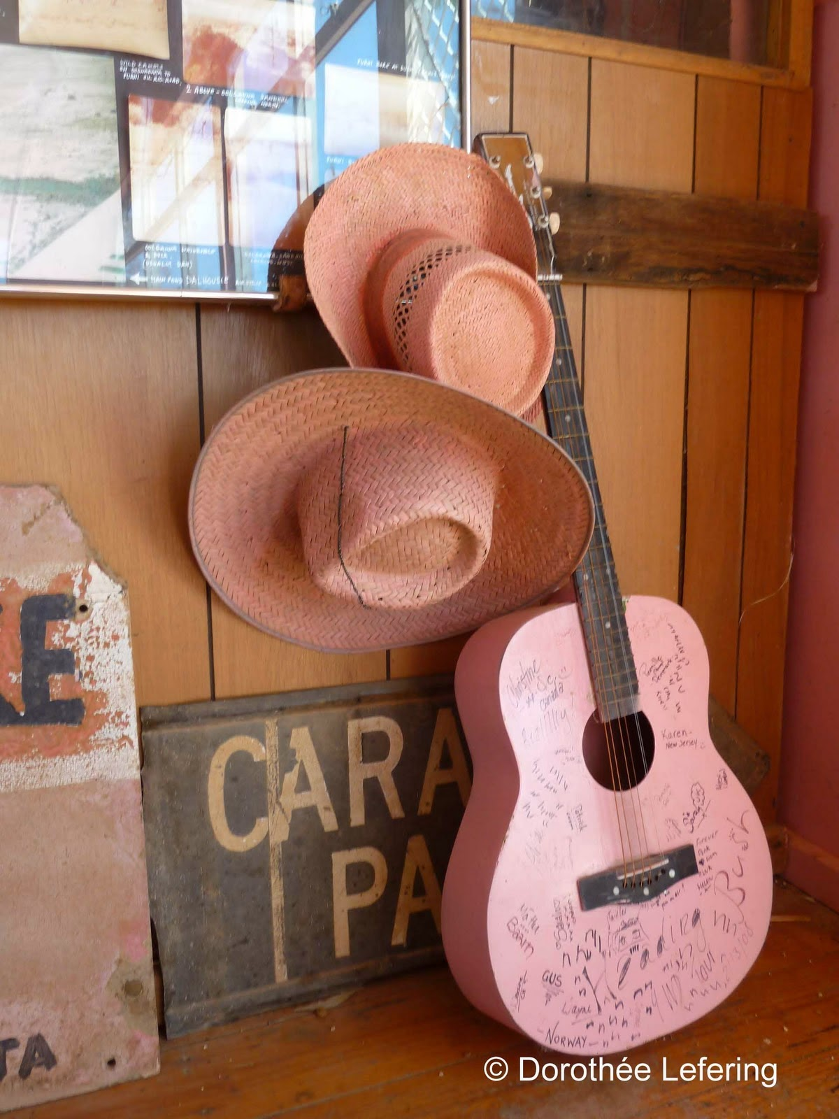A pink guitar and two pink hats leaning against a wall.