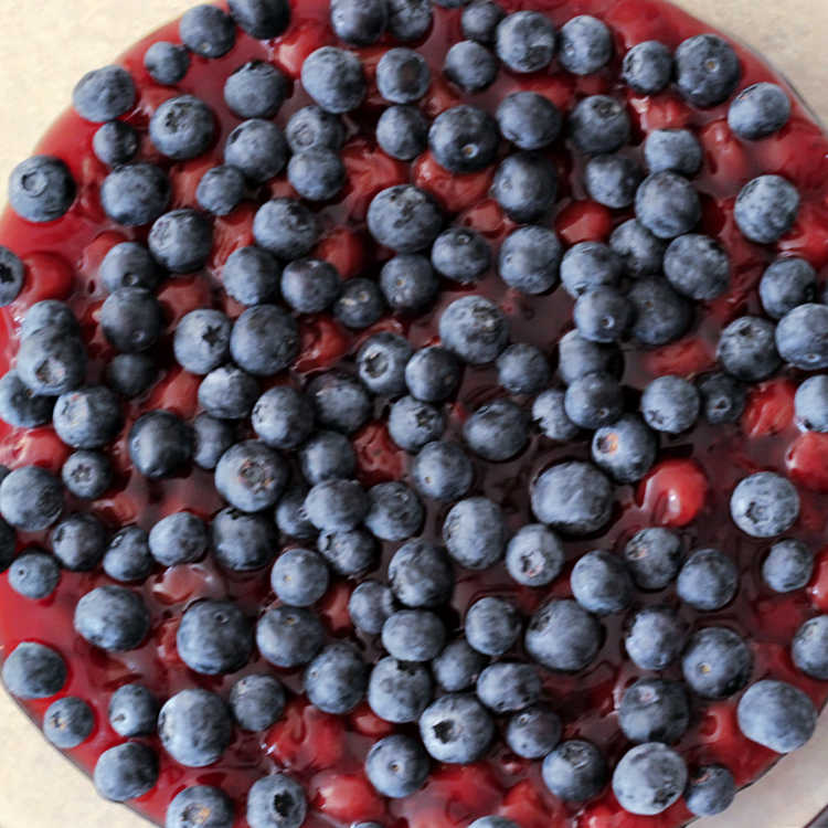 Process image of layer of fresh blueberries over cherry pie filling for red, white, and blueberry dump cake recipe.