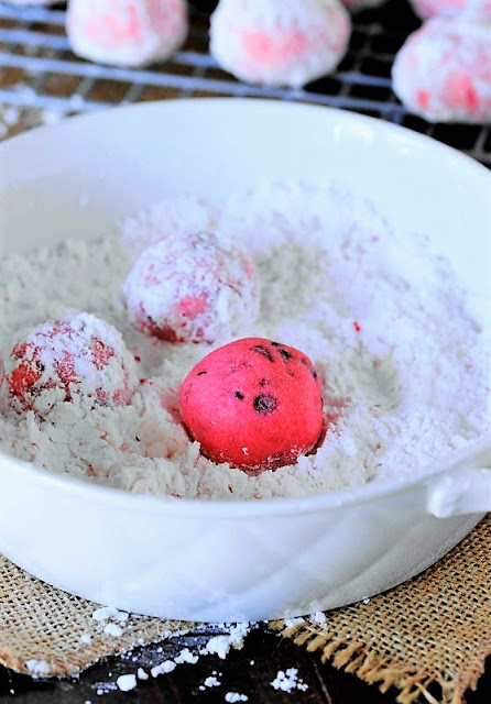 Rolling Peppermint Chocolate Chip Snowball Cookies in Powdered Sugar Image