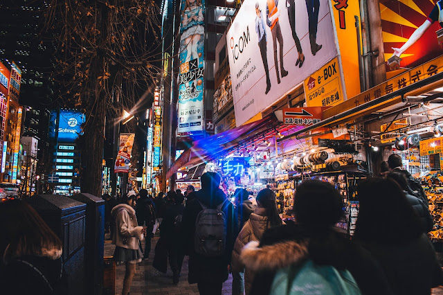 Locals and tourists walking and shopping around electric town Akihabara district at night