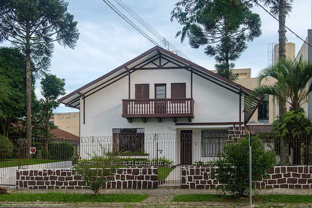 Casa branca com sacada marromcom detalhes decorativos na fachada