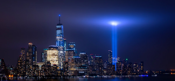 With the Freedom Tower standing proudly nearby, two beams of light representing the fallen World Trade Center complex shoot up into the night sky above New York City.