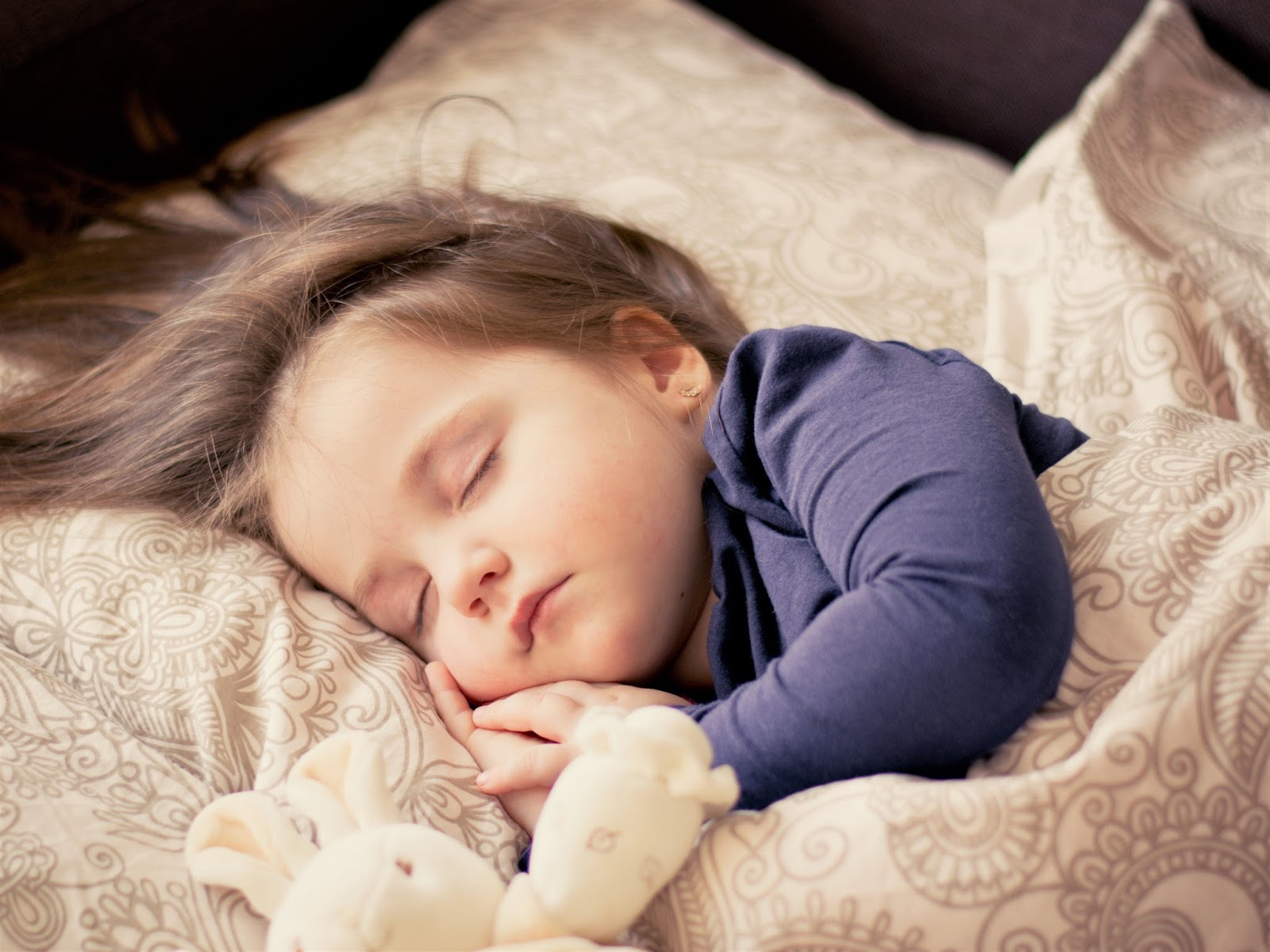 sleeping child with toy rabbit