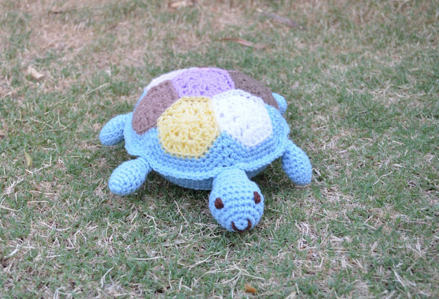 A blue crocheted turtle crawling across the lawn. The pattern on the shell is made of coloured hexagons.  The turtle has a happy smile on its face.