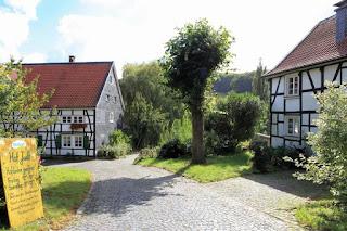Ein Bauernhof, bestehend aus zwei Fachwerkhäusern, die ein Dach aus roten Ziegeln haben