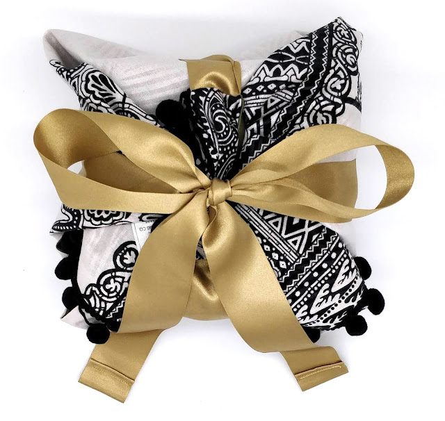 A black and white fabric gift wrap tied up with a gold satin ribbon