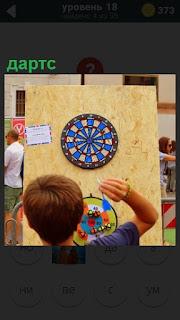 Мальчик играет в дартс, бросает стрелы, пытаясь попасть в цель