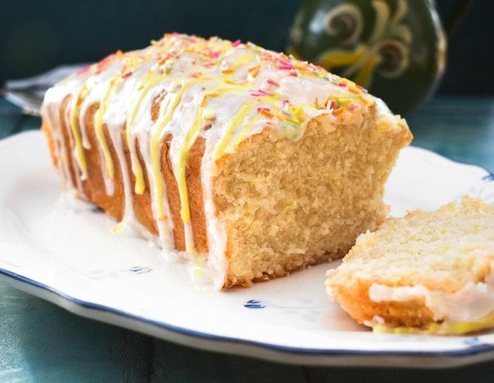 A close up of sliced vegan lemon drizzle cake on a white ceramic platter