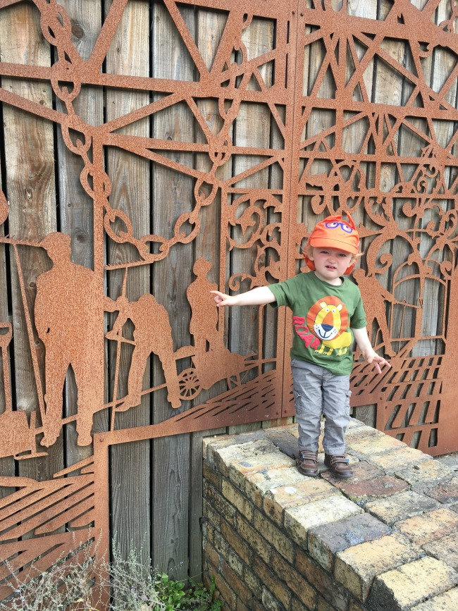 Blaenavon-Ironworks-A-Toddler-in-front-of-fantastic-ironwork-pulling-a-face
