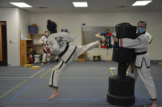 A martial arts black belt lady doing a jump back kick and breaking a wooden board