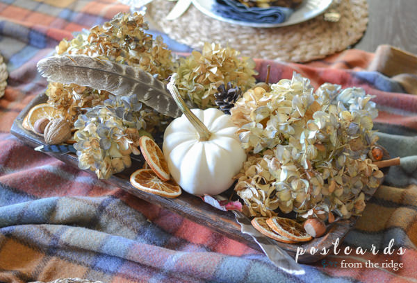 wood dough bowl with dried hydrangeas, dried oranges, nuts, acorns, feathers