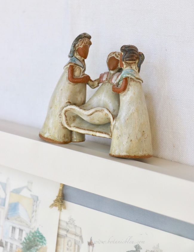 A handmade clay figurine is of three young French girls dressed in vintage clothing
