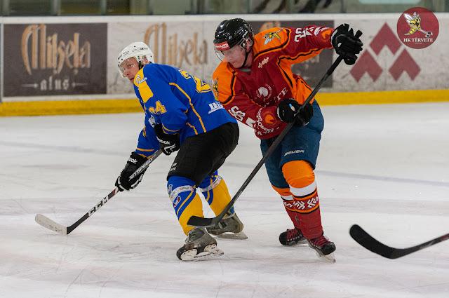 Hokejists mēģina apslidot pretinieku, kurš pagriezies pret viņu ar muguru