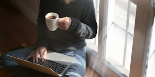 A woman sits cross-legged on the floor under a window, with a laptop on her lap and a cup of coffee in one hand, while the other operates the laptop.