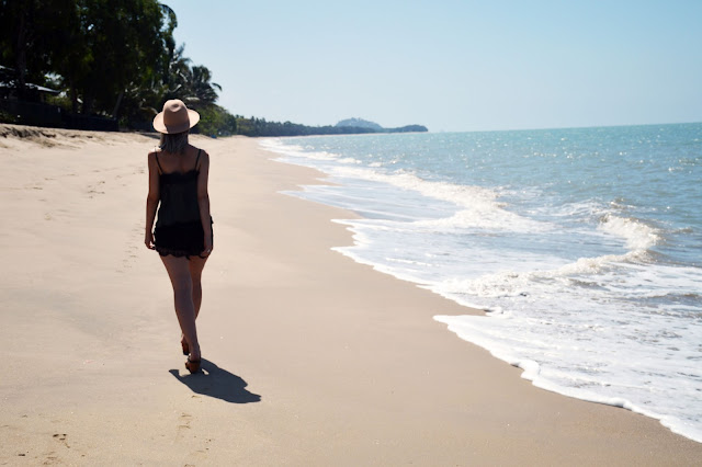 wanderlust girl walking along tropical cairns beach wearing a lace cami slip and lace shorts
