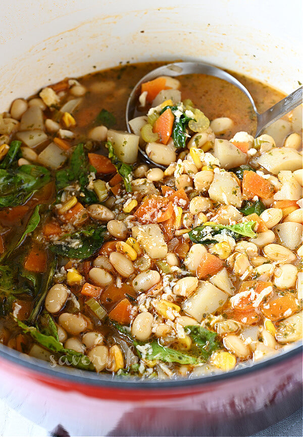 close up of a soup pot with vegetables,parmesan and white beans soup