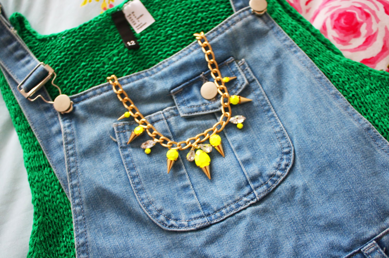 A closeup of an outfit with denim dungarees and knitwear