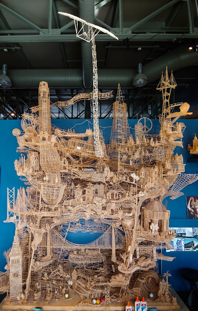 Nine foot tall structure made out of toothpicks that depicts landmarks and significant icons of San Francisco from 1974 to 2011, built by Scott Weaver. Structure has multiple paths that ping pong balls roll down to highlight San Francisco themes and eras.