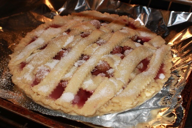 this is a cherry pie baking on foil in the oven