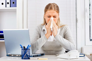 woman blowing nose at work
