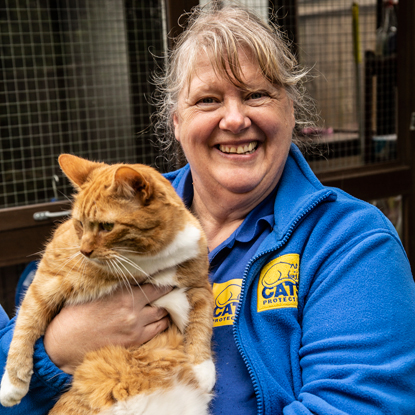 Cats Protection volunteer holding ginger and white cat